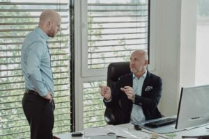 Ein sitzender Geschäftsmann zeigt mit seinen Händen einem stehenden Mann etwas