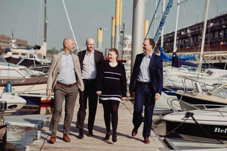 Drei Geschäftsmänner und eine Geschäftsfrau gehen über einen Bootsanleger