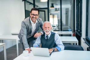 Ein Mann sitzt vor einem Laptop während ein jüngerer Mann sich an diesen anlehnt und beide in die Kamera lächeln