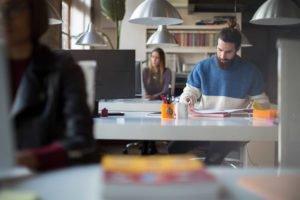 Mann sitzt an einem Schreibtisch und liest Unterlagen