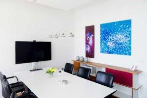 Büro mit einem Fernseher und einem Besprechungstisch