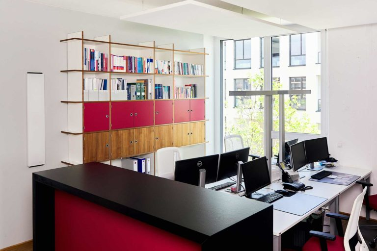 Büro mit vier Tischen, Monitoren und einem Ordnerregal