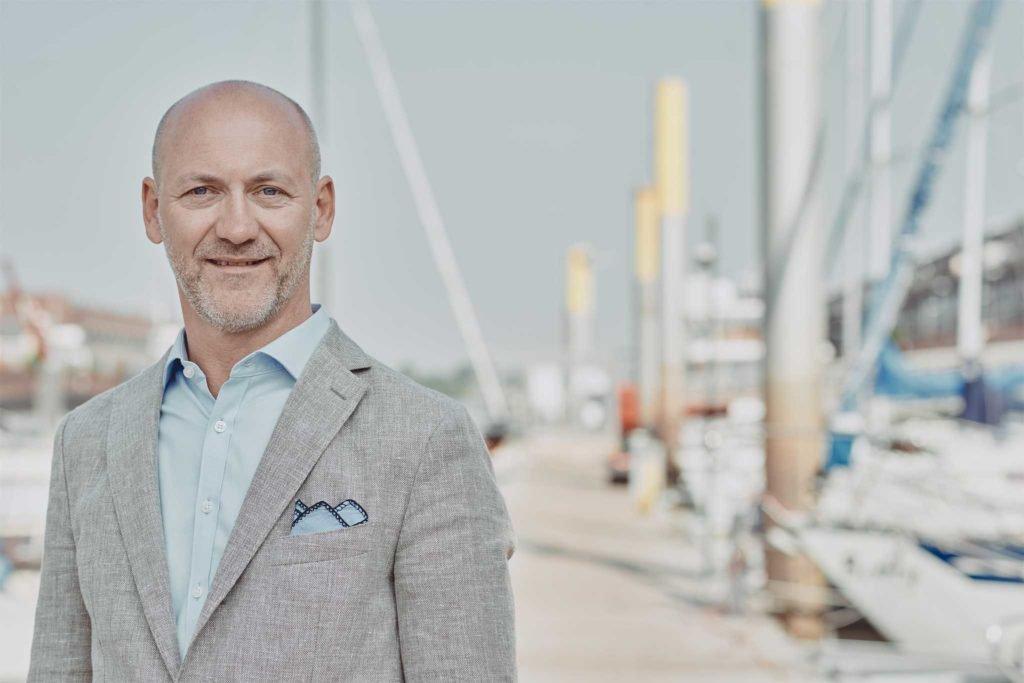 Geschäftsmann mit blauem Hemd und grauem Sakko steht vor Booten