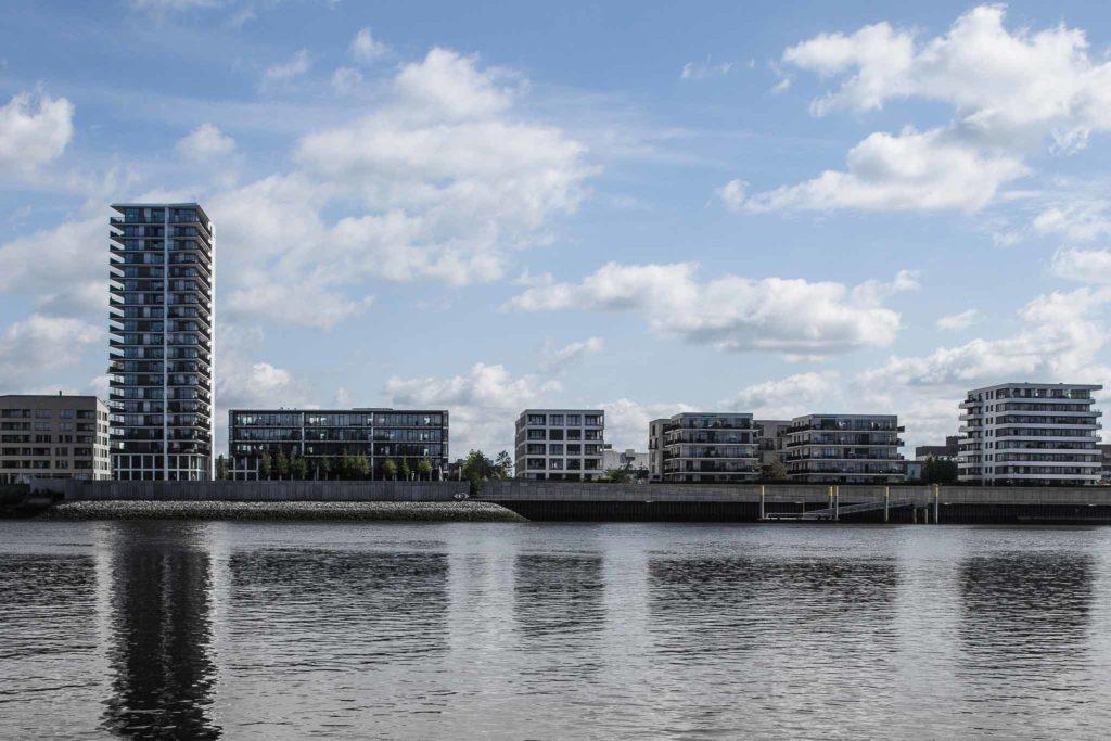 Ansicht auf eine Reihe von Bürogebäuden von einer andere Flussseite aus